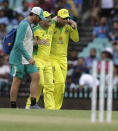 Australia's David Warner, centre, is assisted from the field after injuring himself while fielding during the one day international cricket match between India and Australia at the Sydney Cricket Ground in Sydney, Australia, Sunday, Nov. 29, 2020. (AP Photo/Rick Rycroft)