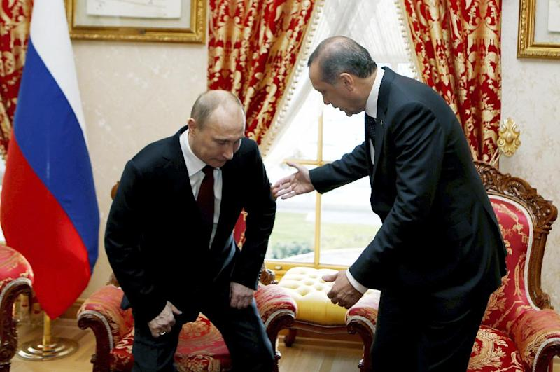 Russian President Vladimir Putin, left, sits down as Turkey's Prime Minister Recep Tayyip Erdogan looks on before a meeting in Istanbul, Turkey, Monday, Dec. 3, 2012. Putin visits Turkey on a one-day trip expected to focus on economic issues as well as differing views over how to resolve the Syrian conflict.(AP Photo/Tolga Bozoglu, Pool)
