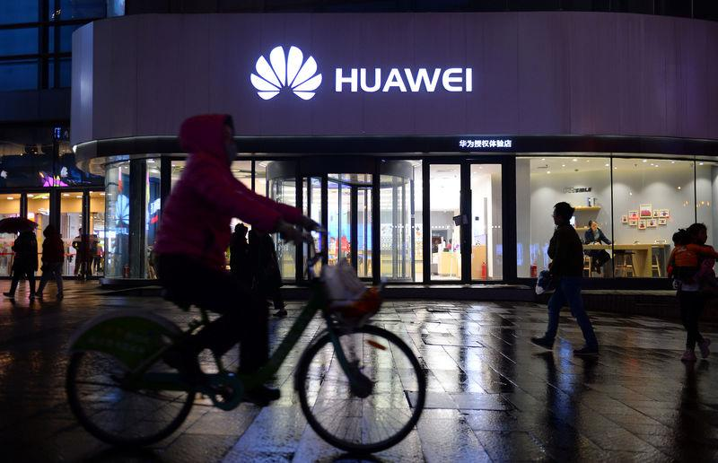 Woman cycles past a Huawei store in Shenyang