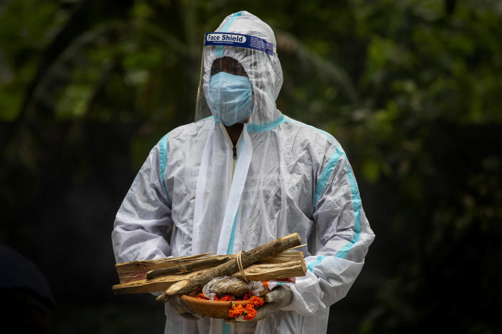 A relative in protective suit waits to perform last rituals near the body of a person who died of COVID-19 during cremation in Gauhati, India, Monday, May 24, 2021. India crossed another grim milestone Monday of more than 300,000 people lost to the coronavirus as a devastating surge of infections appeared to be easing in big cities but was swamping the poorer countryside. (AP Photo/Anupam Nath)