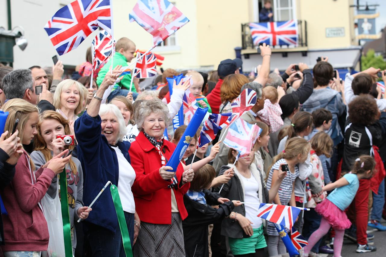 ST PETER PORT, GUERNSEY - JULY 15:  In this handout image provided by LOCOG, Spectators line the route of the Torch Relay leg through St Peter Port on Day 58 of the London 2012 Olympic Torch Relay on July 15, 2012 in Guernsey, Channel Islands. The Olympic Flame is now on day 58 of a 70-day relay involving 8,000 torchbearers covering 8,000 miles.  (Photo by LOCOG via Getty Images)
