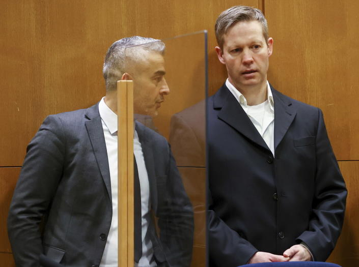 Main defendant Stephan Ernst, right, talks to his his lawyer Mustafa Kaplan, left, in the courtroom at the higher regional court in Frankfurt, Germany, Thursday, Jan. 28, 2021. The German court has convicted the 47-year-old far-right extremist Stephan Ernst of the murder of Walter Luebcke, a regional politician, in a brazen killing that shocked the country, and sentenced to life in prison. (Kai Pfaffenbach/Pool Photo via AP)