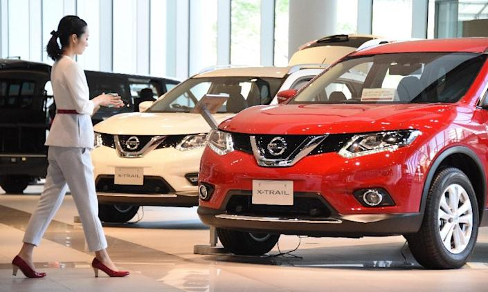 A staff member talks in front of vehicles at the showroom of the headquarters of Japan's number two automaker Nissan Motor in Yokohama, suburban Tokyo, on May 13, 2016 (AFP Photo/Toru Yamanaka)
