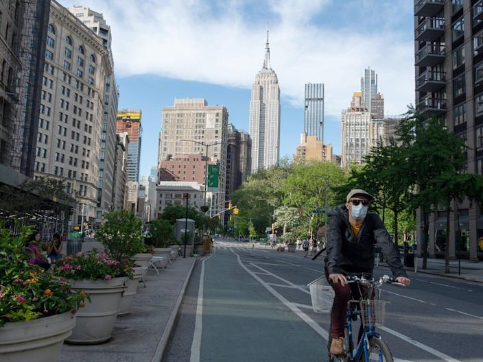 A person wearing a mask rides a bike in Flatiron as the Empire State Building can be seen in the background amid the coronavirus pandemic on May 16, 2020 in New York City.