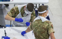 Soldiers carry out mass coronavirus testing, set up at a marketplace in Liverpool, England, during the four-week national lockdown to curb the spread of coronavirus in England, Wednesday Nov. 11, 2020. Everyone in Liverpool city, are being encouraged to be tested for COVID-19, even if they are not displaying symptoms, as authorities continue a mass testing pilot scheme to suppress the coronavirus.(Peter Byrne/PA via AP)