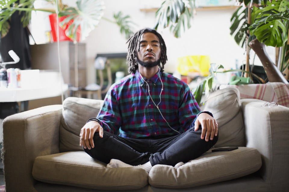Serene young man meditating with headphones on apartment sofa