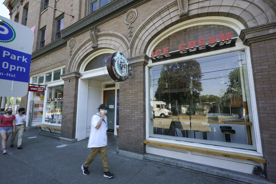 A person walks past a Molly Moon's Ice Cream store in Seattle's Capitol Hill neighborhood, Monday, June 28, 2021, in Seattle. The store was closed Monday due to excessive heat as Seattle and other cities in the Pacific Northwest endured the hottest day of an unprecedented and dangerous heat wave on Monday, with temperatures obliterating records that had been set just the day before on Sunday. (AP Photo/Ted S. Warren)
