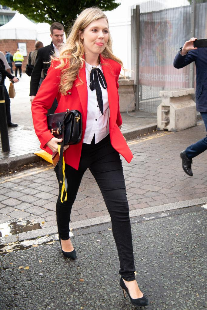 Carrie Johnson arrives at the Conservative Party Conference in Manchester in a red blazer and ribbon-tie blouse, both from Zara. (Getty Images)