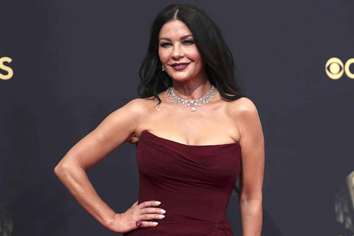 """<p>With lifelong beauty inspirations like <a href=""""https://people.com/style/catherine-zeta-jones-launches-lipstick-and-lip-liner/"""" rel=""""nofollow noopener"""" target=""""_blank"""" data-ylk=""""slk:Eva Gardner, Rita Hayworth, Sophia Loren and Elizabeth Taylor"""" class=""""link rapid-noclick-resp"""">Eva Gardner, Rita Hayworth, Sophia Loren and Elizabeth Taylor</a>, glamour is second-nature to <a href=""""https://people.com/tag/catherine-zeta-jones/"""" rel=""""nofollow noopener"""" target=""""_blank"""" data-ylk=""""slk:Catherine Zeta-Jones"""" class=""""link rapid-noclick-resp"""">Catherine Zeta-Jones</a>. Attending both to present and support <a href=""""https://people.com/tv/2021-emmy-awards-catherine-zeta-jones-fangirls-over-husband-michael-douglas-nomination/"""" rel=""""nofollow noopener"""" target=""""_blank"""" data-ylk=""""slk:husband and nominee Michael Douglas"""" class=""""link rapid-noclick-resp"""">husband and nominee Michael Douglas</a>, the actress made a grand entrance in <a href=""""https://people.com/style/2021-emmy-awards-best-dressed-stars/?slide=b24e6702-cab2-4576-a3f7-5664e9627e51#b24e6702-cab2-4576-a3f7-5664e9627e51"""" rel=""""nofollow noopener"""" target=""""_blank"""" data-ylk=""""slk:a ruched maroon strapless gown"""" class=""""link rapid-noclick-resp"""">a ruched maroon strapless gown</a>, which she matched from head – with her coordinating lip color – to toe. Mega-watt lashes (using <a href=""""https://www.wunder2.com/products/my-mascara"""" rel=""""nofollow noopener"""" target=""""_blank"""" data-ylk=""""slk:her very own mascara"""" class=""""link rapid-noclick-resp"""">her very own mascara</a>) and relaxed waves completed her icon IRL look.</p>"""