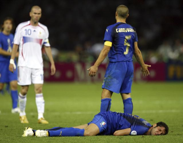 FILE - In this Sunday, July 9, 2006, file photo, France's Zinedine Zidane, left, looks on as Italy's Marco Materazzi lies injured, and Italy's Fabio Cannavaro reacts, during extra time in the World Cup final soccer match between Italy and France, at the Olympic Stadium, in Berlin. Zidane, television replays had shown, had head-butted Materazzi, and he was sent off. Italy won the ensuing penalty shootout. The 21st World Cup begins on Thursday, June 14, 2018, when host Russia takes on Saudi Arabia. (AP Photo/Jasper Juinen, File)