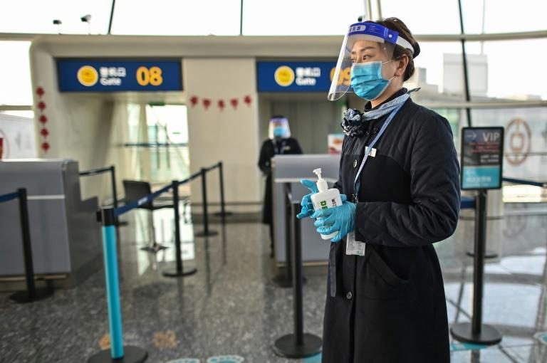 An airline worker wearing a face mask at the airport in Wuhan on February 12, 2021