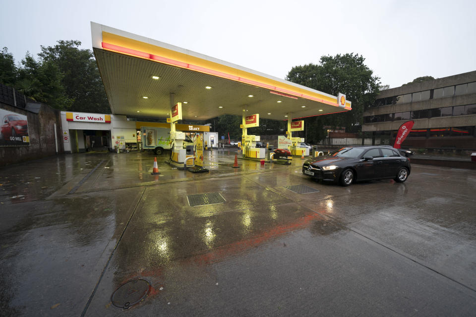 A car drives through the forecourt of a petrol station in Manchester which has run out of fuel after an outbreak of panic buying in the UK, Monday, Sept. 27, 2021. British Prime Minister Boris Johnson is said to be considering whether to call in the army to deliver fuel to petrol stations as pumps ran dry after days of panic buying. (AP Photo/Jon Super)