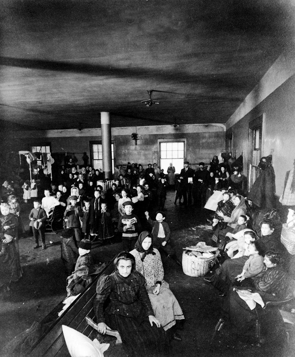 <p>A group of immigrants in the Ellis Island processing center await the next step in attaining an American citizenship. </p>