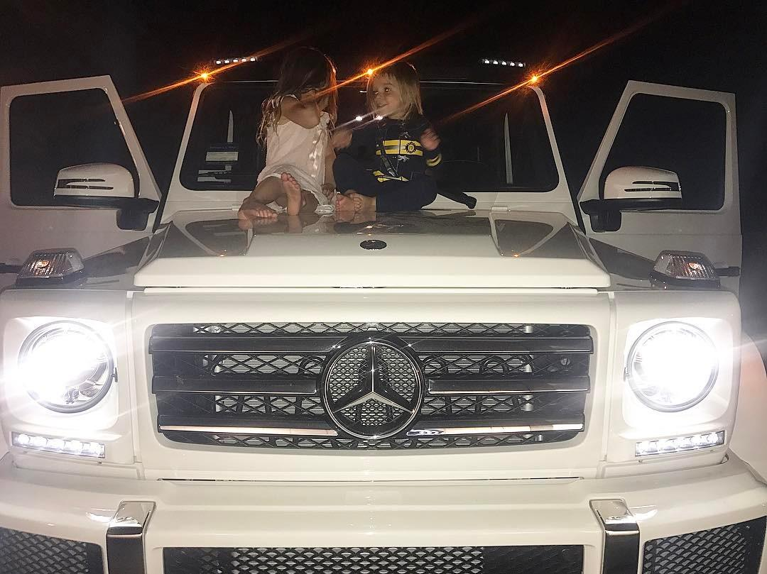 Uh, OK, cool, Kourt. We get that you have $$$. No need to post a pic of your massive Mercedes + your tiny tots (pictured: Penelope and Reign, two-thirds of her brood).