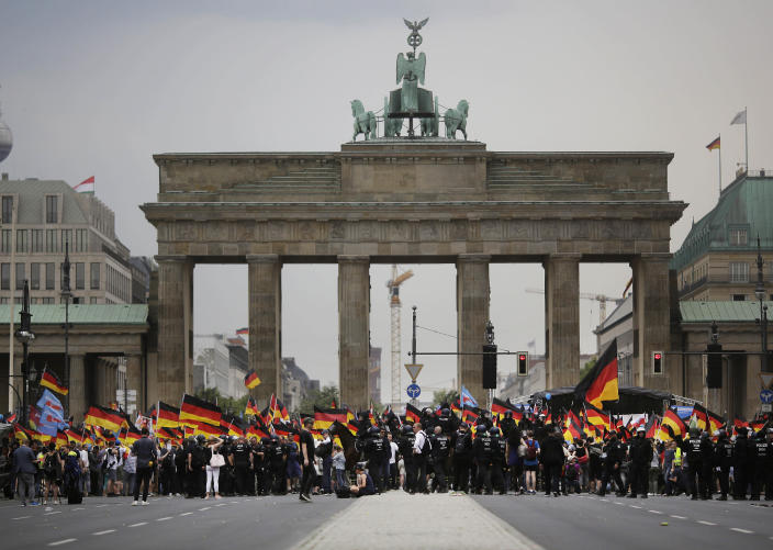 FILE - In this Sunday, May 27, 2018 file photo, AfD supporters wave flags in front of the Brandenburg Gate in Berlin, Germany. Migration is a side issue in this year's German election campaign for the national elections on Sept. 26, but that hasn't stopped the country's biggest far-right party from trying to play it up. (AP Photo/Markus Schreiber, File)