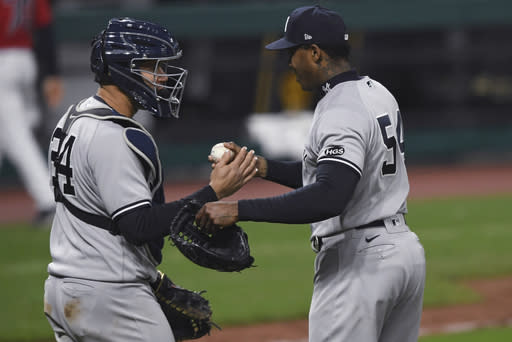 New York Yankees relief pitcher Aroldis Chapman (54) is congratulated by catcher Gary Sanchez after the Yankees defeated the Cleveland Indians 10-9 in Game 2 of an American League wild-card baseball series, early Thursday, Oct. 1, 2020, in Cleveland. (AP Photo/David Dermer)