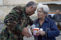 Doctor Aram Gregorian gives drugs to a woman near her apartment building during a military conflict in Stepanakert, the separatist region of Nagorno-Karabakh, Friday, Oct. 16, 2020. As Nagorno-Karabakh's medical system faced a massive challenge, volunteers joined the fight against the virus, delivering medicines to the people hiding in basements and helping track down those infected. (AP Photo)