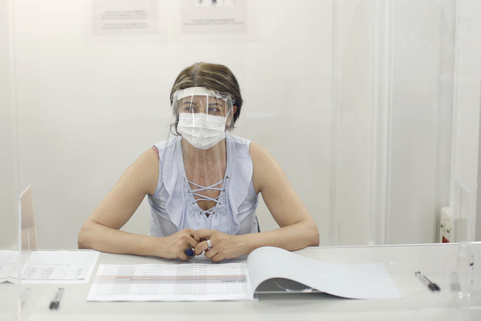 A woman wearing a face mask and visor to protect against coronavirus sits behind a glass shield during a rehearsal of the vote for the local elections scheduled for Sunday, June 28, in Paris, Friday, June 26, 2020. France is to hold its Covid-19 delayed second round of local elections on June 28. (AP Photo/Thibault Camus)