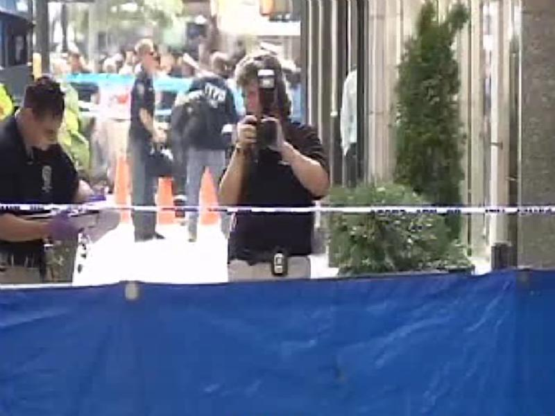 In this frame grab from AP video, authorities photograph the scene where a body lies after a shooting near the Empire State Building, Friday, Aug. 24, 2012, in New York. At least four people were shot outside New York City's Empire State Building on Friday morning and the gunman was dead, New York City officials said. A witness said the gunman was firing indiscriminately. (AP Photo/AP video)