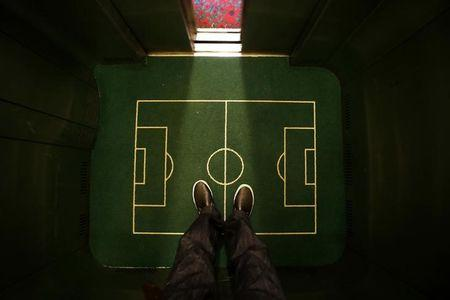 A  floor cover depicting a soccer pitch is seen in an elevator in a hotel in Curitiba