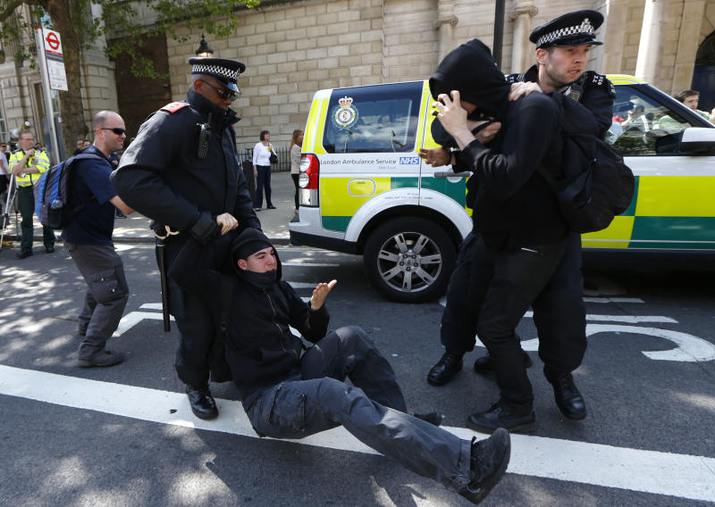 Police officers drag two counter demonstrators, United Against Fascism's supporters, away from a confrontation with English Defence League's supporters at Whitehall, London Monday, May 27, 2013. EDL supporters marched to Downing Street to protest in support of the British armed forces, after the brutal killing of an off-duty British soldier in a London street last week.(AP Photo/Sang Tan)