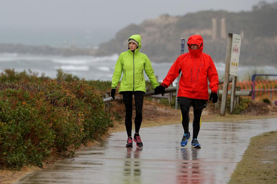 Couple hold hands as they walk in the rain.