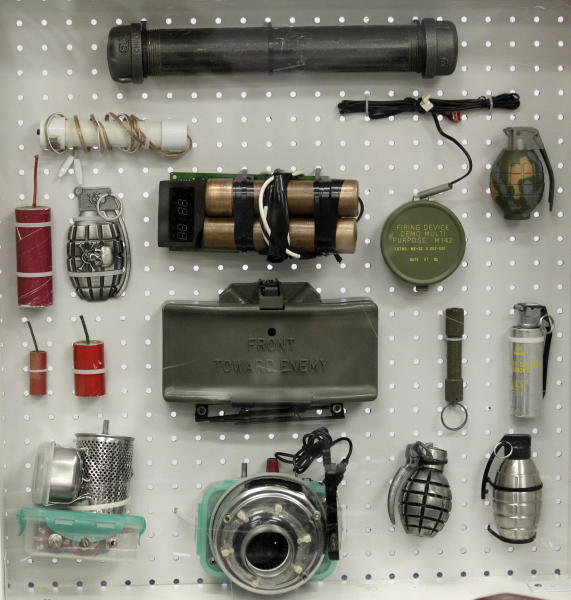 FILE - In this Nov. 17, 2011 file photo, items confiscated by the Transportation Security Administration are on display at the TSA's training center at Newark Liberty International Airport in Newark, N.J. Among the items is a replica M18 claymore mine, center, a fake dynamite bomb, and home-made electronics, lower left. After a man was arrested at Los Angeles International Airport wearing a bulletproof vest, flame-resistant pants and had a suitcase full of weapons, the TSA has restated what air travelers are allowed to bring along. (AP Photo/Julio Cortez)