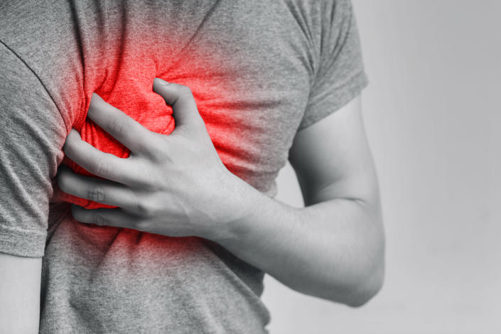 Acute pain in chest, man touching his inflamed breast, close-up