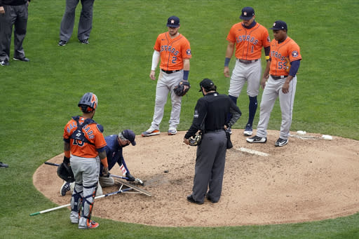 Houston Astros reliever pitcher Framber Valdez, right, waits as a grounds crew worker re-grooms an area of the mound before Valdez resumed pitching against the Minnesota Twins in the fifth inning in Game 1 of an American League wild-card baseball series, Tuesday Sept. 29, 2020, in Minneapolis. (AP Photo/Jim Mone)