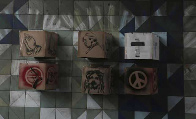 <p>Boxes featuring images of praying hands, the pope, a cross, a gun, Jesus and a peace sign are attached to the wall of a highway underpass, placed by opposition protesters during a national sit-in against President Nicolas Maduro, in Caracas, Venezuela, Monday, May 15, 2017. (AP Photo/Fernando Llano) </p>