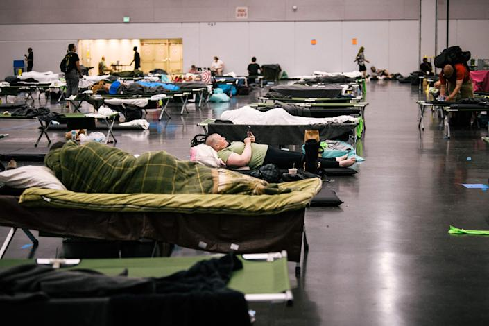 People rest at the Oregon Convention Center 'cooling station' during last month's record heat (AFP via Getty Images)