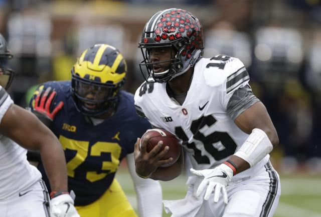 "Ohio State quarterback <a class=""link rapid-noclick-resp"" href=""/ncaaf/players/225823/"" data-ylk=""slk:J.T. Barrett"">J.T. Barrett</a> (16) rushes during the first half of an NCAA college football game against Michigan, Saturday, Nov. 25, 2017, in Ann Arbor, Mich. (AP Photo/Carlos Osorio)"