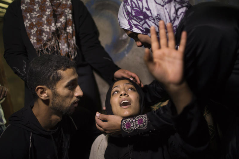 The mother of 10-month-old Palestinian infant Haneen Tafesh is comforted by relatives prior the funeral in Jabaliya, north Gaza, Friday, Nov. 16, 2012. According to hospital reports Tafesh died from wounds of an earlier Israeli strike. (AP Photo/Bernat Armangue)