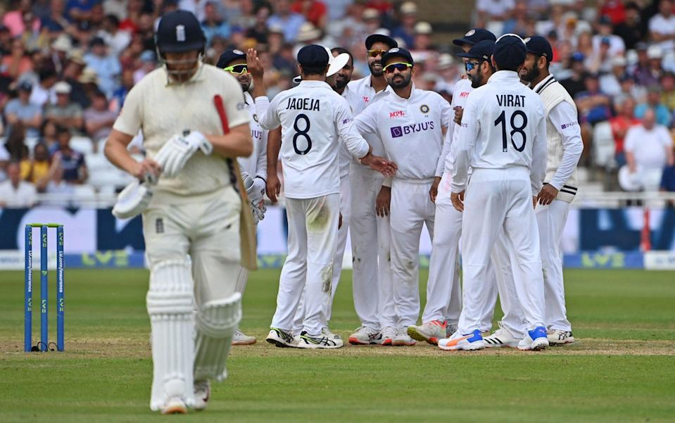 India's players celebrate as England's Jonny Bairstow walks back to the pavilion after losing his wicket for 29 during play on the first day of the first cricket Test match of the India Tour of England 2021 between England and India at the Trent Bridge cricket ground in Nottingham, central England on August 4, 2021. - AFP