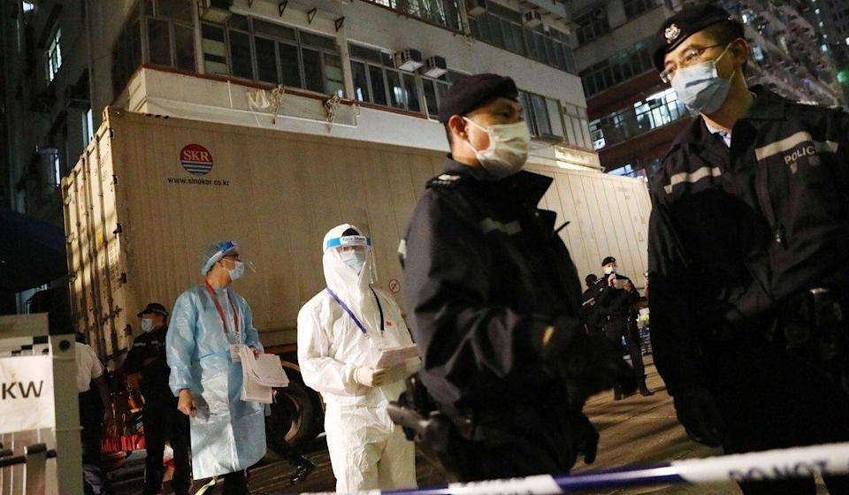 Police and government workers at the site in Yau Ma Tei after it was locked down at 7pm. Photo: K. Y. Cheng
