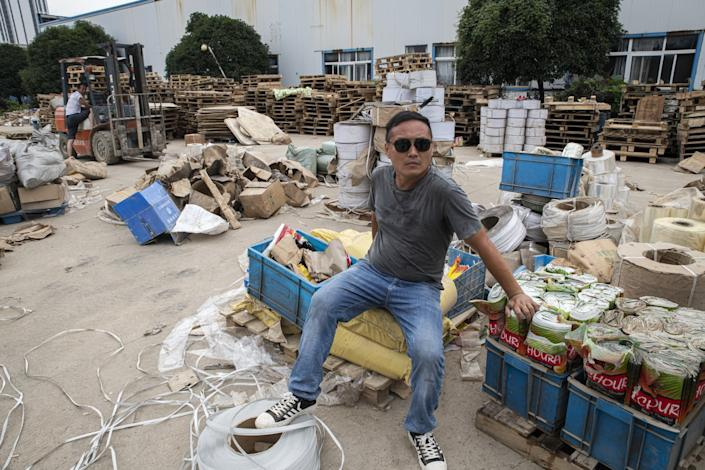 "Ma Dacong, a waste collector, sits among flooded gear to be disposed of at a tea factory in Shexian, Anhui province. <span class=""copyright"">(Liu Bowen / For The Times)</span>"