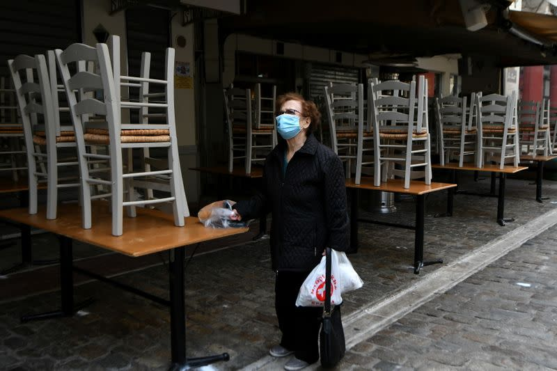 A woman stands outside a closed restaurant, amid the coronavirus disease (COVID-19) pandemic, in Thessaloniki