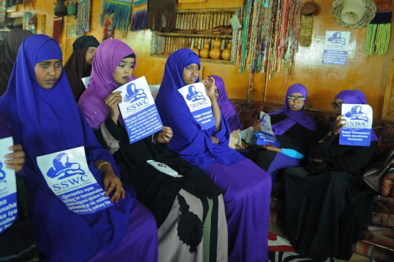 """Somali female activists, holding messagesthat read """"Save Somali Women and children,"""" gather to mark International Women's Day."""