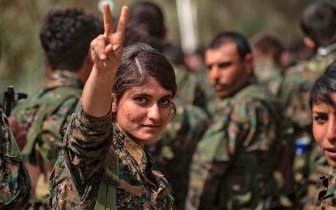 A female fighter of the US-backed Kurdish-led Syrian Democratic Forces (SDF) flashes the victory gesture while celebrating after announcing the total elimination of the Islamic State in Syria - Credit: AFP
