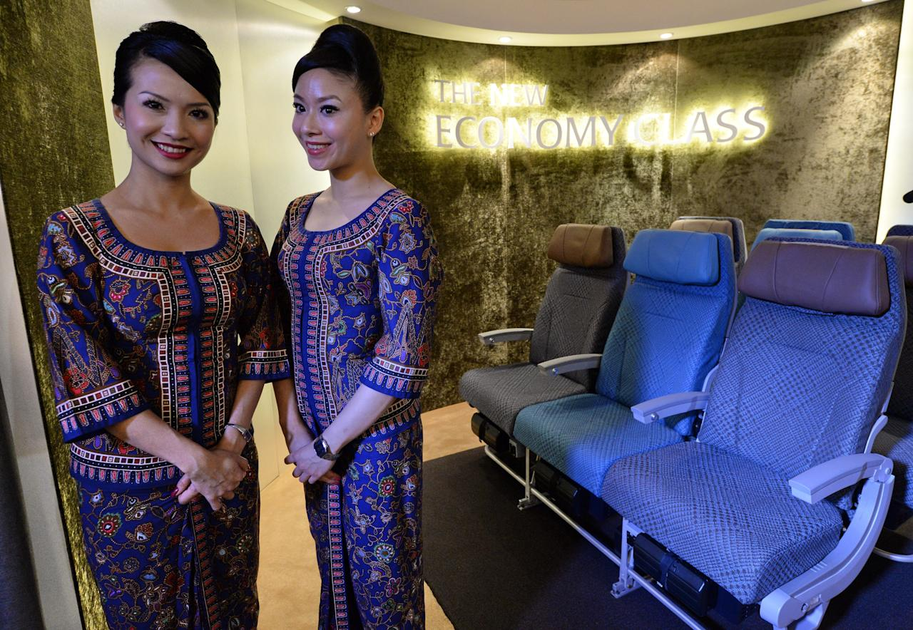 A Singapore Airlines (SIA) stewardesses stand next to a display of the new Singapore Airlines Economy Class seats during their next generation cabin product launch in Singapore on July 9, 2013. SIA on July 9 unveiled new seats and other in-flight amenities as part of a sweeping upgrade of its cabins amid intensifying competition in the industry. AFP PHOTO / ROSLAN RAHMAN