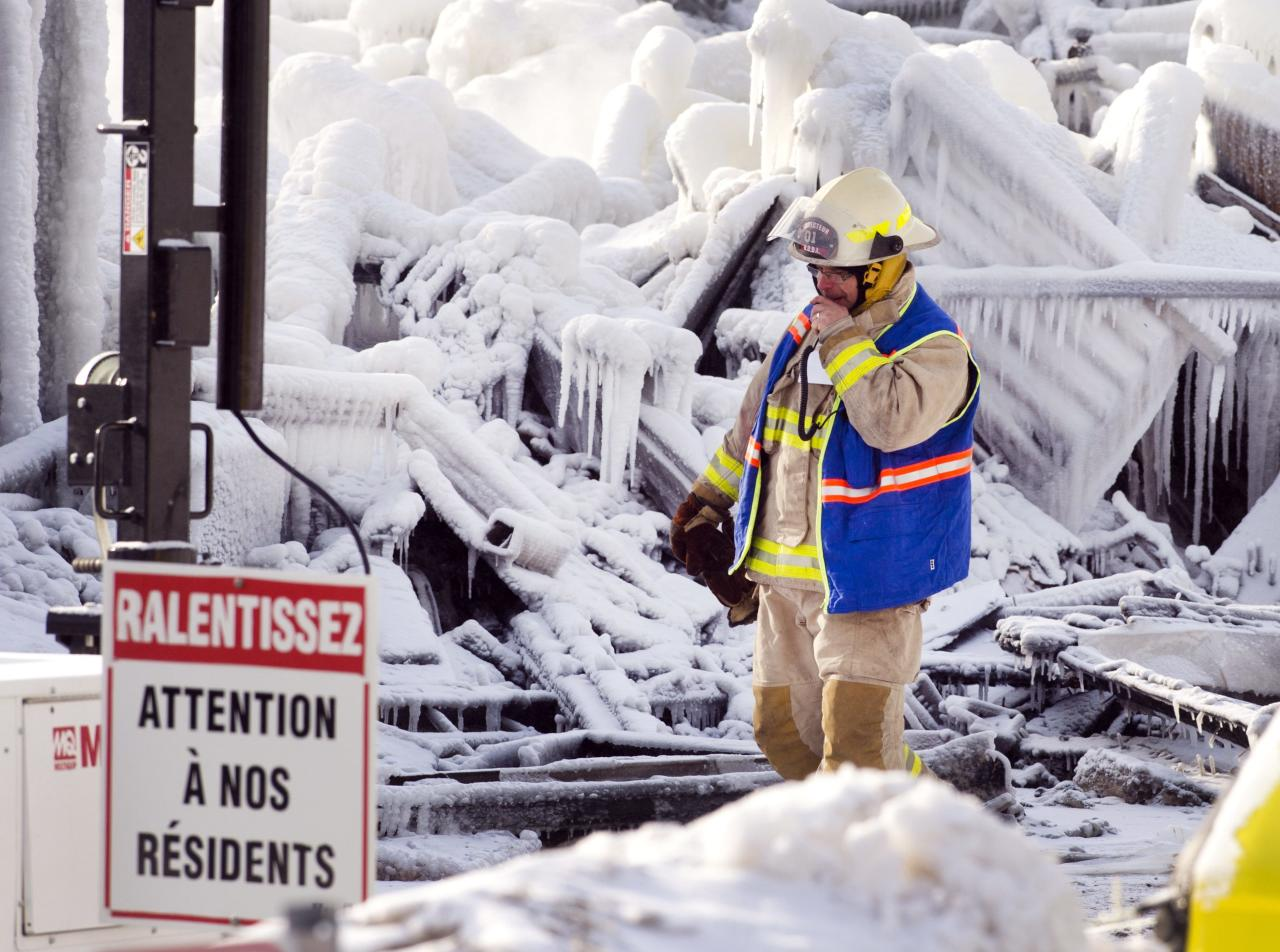 "An emergency worker walks past a sign that reads ""Look out for our residents"" as they search through the icy rubble of a fire that destroyed a seniors' residence Friday, Jan. 24, 2014, in L'Isle-Verte, Quebec. Five people are confirmed dead and 30 people are still missing, while with cause of Thursday morning's blaze is unclear police said. Authorities are using steam to melt the ice and to preserve any bodies that are buried. (AP Photo/The Canadian Press, Ryan Remiorz)"