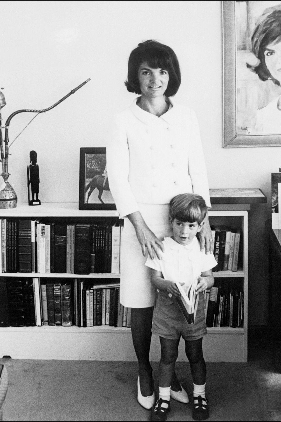 <p>A little suit is not only for state events. Jackie appears in a boxy number in a light hue at home with her son John Jr. in 1964.</p>
