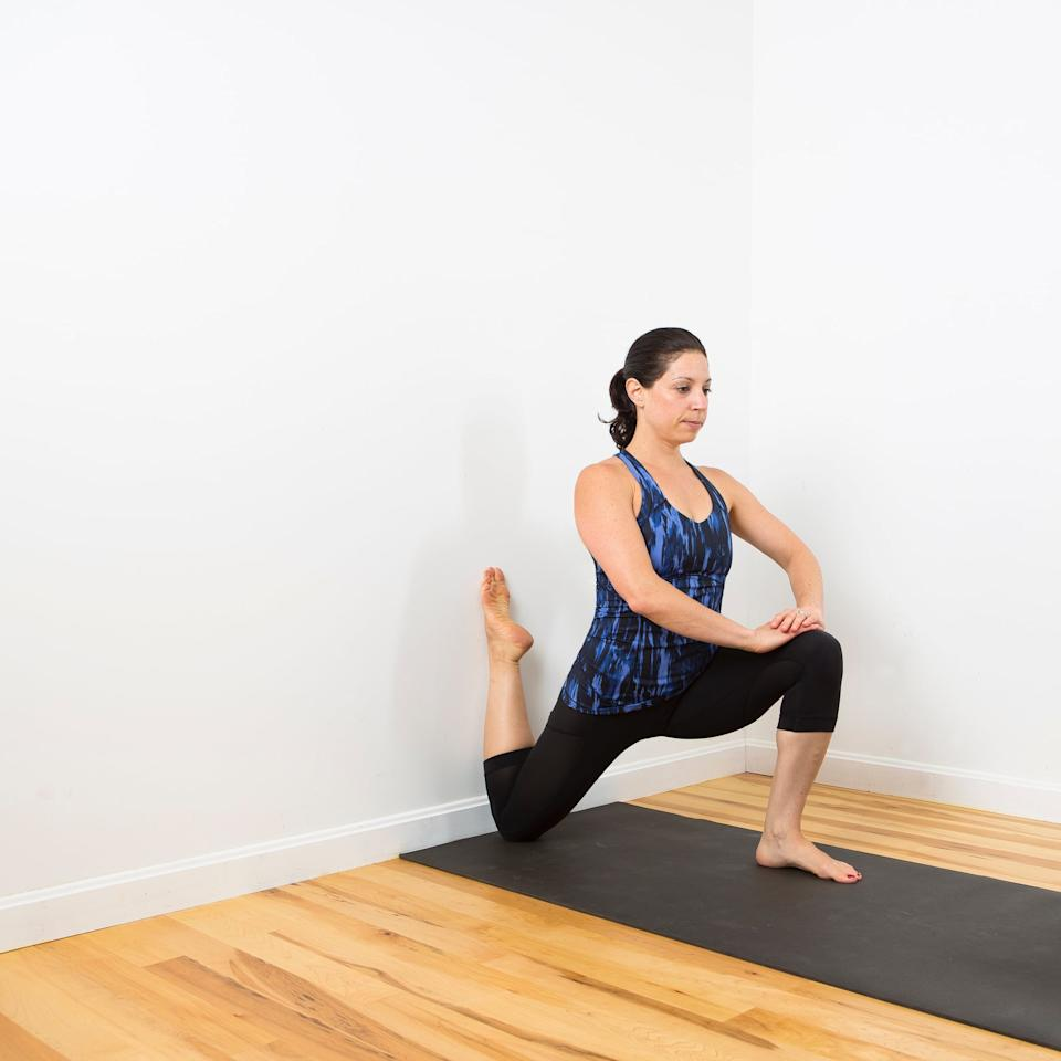 <ul> <li>Kneel down and place your right knee as close as you can to the wall, resting your toes against the wall. I like to rest my bottom knee on an AbMat, but you can also use a folded up mat or towel.</li> <li>Place your left foot on the ground in front of you, and lower your hips until you feel a stretch in the front of your right hip.</li> <li>Place your hands on your front knee to keep your spine long. </li> <li>Stay like this for five or more breaths. Slowly release and do this stretch on the other side.</li> </ul>
