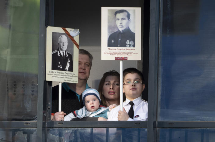 Ermakov's family who cannot go outside to celebrate Victory Day due to coronavirus hold portraits of their ancestors, participants in World War II while standing on the balcony of their apartment in St. Petersburg, Russia, Saturday, May 9, 2020. Victory Day, the anniversary of the defeat of Nazi Germany in World War II, is Russia's most important secular holiday and this year's observance had been expected to be especially large because it is the 75th anniversary, but military parades in Russian cities and a mass processions called The Immortal Regiment were postponed as part of measures to stifle the spread of the virus. (AP Photo/Dmitri Lovetsky)