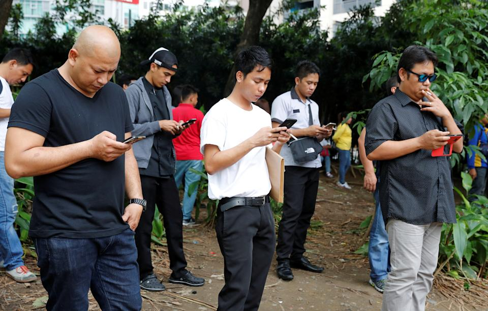 FILE PHOTO: Filipinos use their mobile phones at a park in Taguig, Metro Manila, Philippines, August 2, 2018. Picture taken August 2, 2018. REUTERS/Erik De Castro