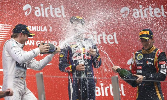 Mercedes Formula One driver Nico Rosberg of Germany (L) and Lotus F1 Formula One driver Romain Grosjean (R) of France spray champagne on the face of Red Bull Formula One driver Sebastian Vettel of Germany on the podium after the Indian F1 Grand Prix at the Buddh International Circuit in Greater Noida, on the outskirts of New Delhi, October 27, 2013. Vettel became Formula One's youngest four-times world champion on Sunday after winning the Indian Grand Prix for Red Bull. REUTERS/Ahmad Masood (INDIA - Tags: SPORT MOTORSPORT F1)