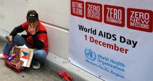 A vendor sits next to a world AIDS day poster