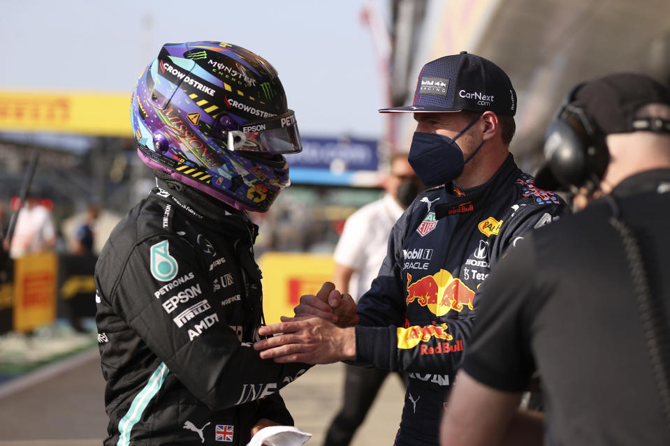 Mercedes driver Lewis Hamilton of Britain, left, shakes hands with Red Bull driver Max Verstappen of the Netherlands at the end of the qualifying session ahead of Sunday's British Formula One Grand Prix, at the Silverstone circuit, in Silverstone, England, Friday, July 16, 2021. Hamilton clocked the fastest time and Verstappen was second. (Lars Baron/Pool photo via AP)