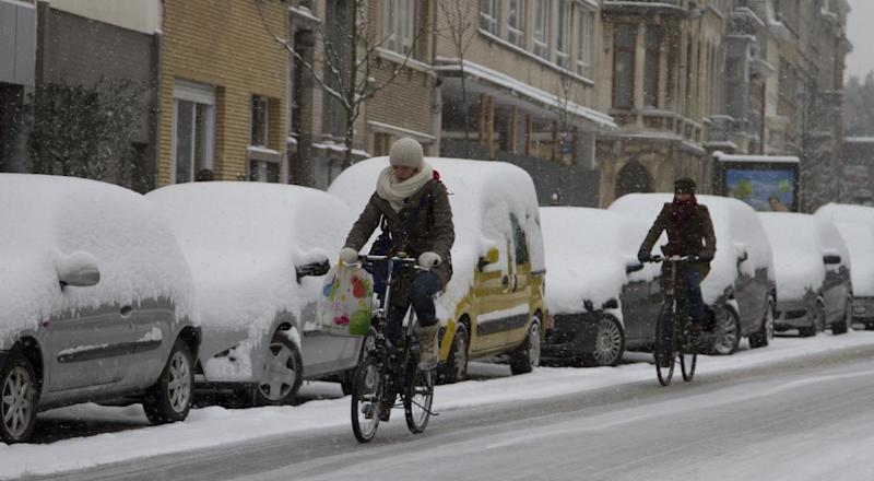 People ride their bicycles on an icy road in Antwerp, Belgium on Tuesday, March 12, 2013. An overnight snowfall on Monday evening snarled rush hour traffic on Tuesday morning. (AP Photo/Virginia Mayo)