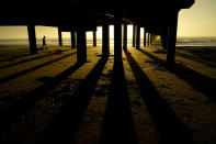 FILE - In this Nov. 21, 2020, file photo, a man walks along the beach under the Horace Caldwell Pier at sunrise in Port Aransas, Texas. (AP Photo/Eric Gay, File)